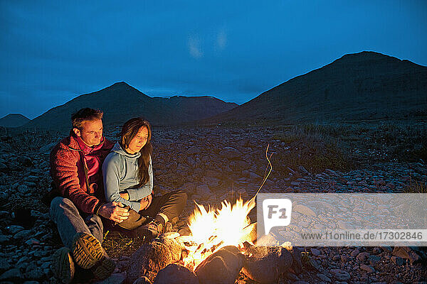 couple sitting by campfire in Iceland
