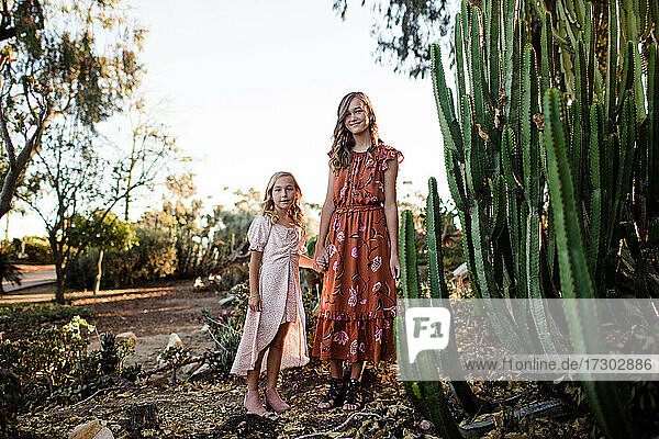 Sisters Holding Hands While Standing in Desert Garden in San Diego