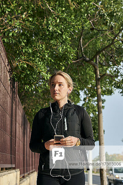 Woman wearing sportswear uses her phone while she is walking
