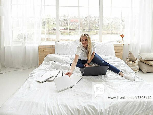 junges blondes Mädchen sitzt auf dem weißen Bett mit Kopierbüchern und Laptop