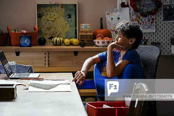 A focused boy with knees inside shirt sits at computer at home