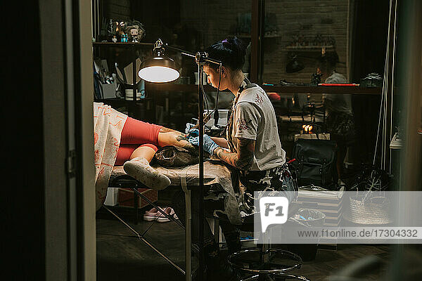 Portrait of a woman tattoo master showing a process of creation tattoo on a hand under the lamp light.