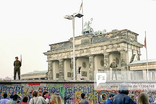 Wall in front of the Brandenburg Gate monitored by two People's Police officers and a camera  November 1989