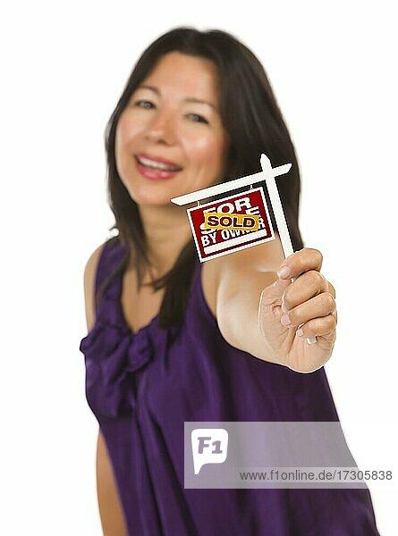 Attraktive multiethnische Frau hält kleine verkauft für Verkauf von Eigentümern Immobilien Zeichen in der Hand vor weißem Hintergrund