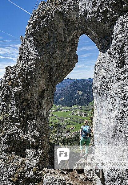 Wanderin steht im Felsentor Breitensteinfensterl mit Ausblick auf Hochnebel über dem Tal  Wanderweg zum Breitenstein  Fischbachau  Bayern  Deutschland  Europa