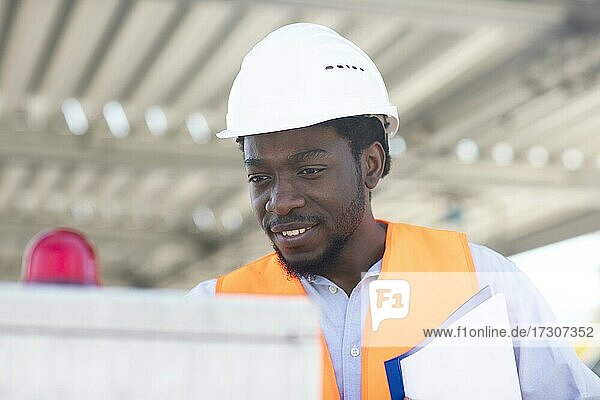 Junger schwarzer Mann arbeitet außen als Techniker mit Helm und Sicherheitsweste  Freiburg  Baden-Württemberg  Deutschland  Europa