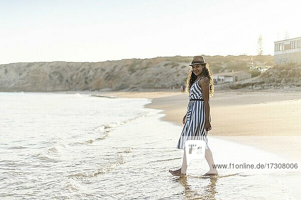 Portrait of a beautiful young woman on the beach by sunset in Algarve  Portugal  Europe