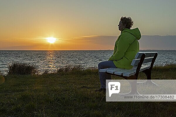 Frau genießt den Sonnenuntergang auf einer Bank  Großenbrode Weststrand  Schleswig-Holstein  Deutschland  Europa