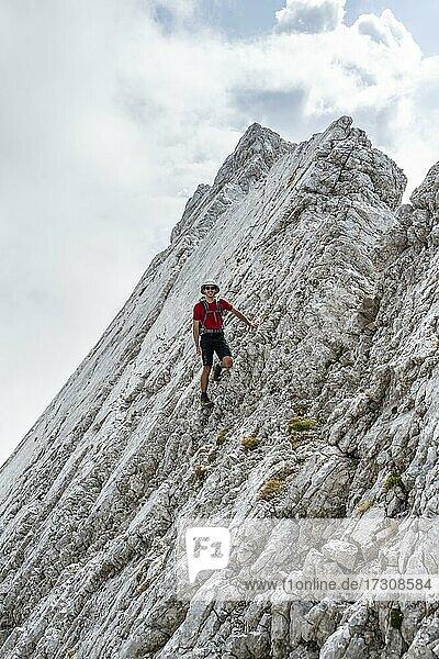 Junger Mann an einer Felswand  Felsige Berge und Geröll  beim Hochkalter  Berchtesgadener Alpen  Berchtesgadener Land  Oberbayern  Bayern  Deutschland  Europa