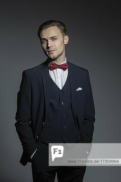 Porträt selbstbewusster  gut aussehender junger Mann im dreiteiligen Anzug