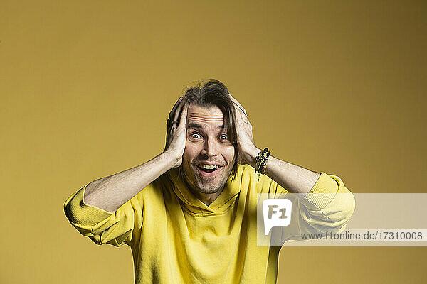 Porträt aufgeregt  überrascht Mann auf gelbem Hintergrund