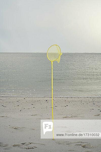 Gelbes Fischernetz im Sand am Meeresstrand