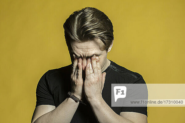 Müder  gestresster junger Mann reibt sich die Augen auf gelbem Hintergrund
