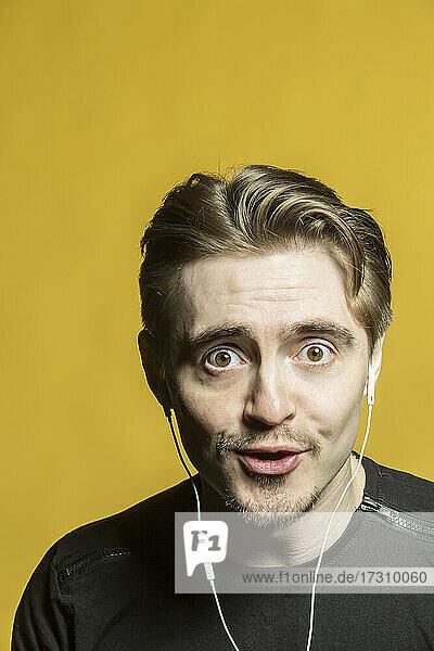 Porträt breitäugiger Mann  der mit Kopfhörern Musik hört