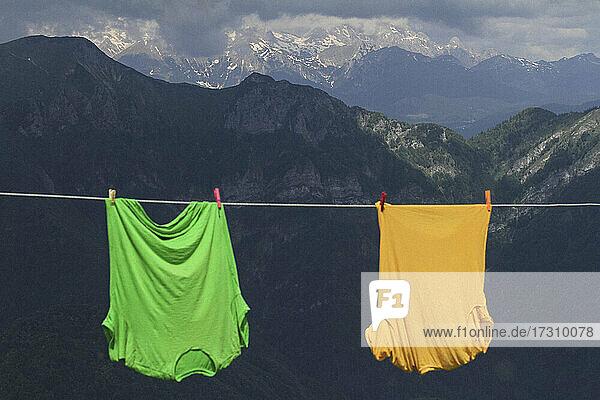 Leuchtend grüne und gelbe T-Shirts hängen auf Wäscheleine in den Bergen  Julische Alpen  Slowenien