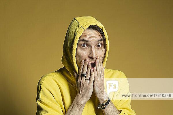 Porträt überrascht junger Mann in gelben Kapuzenpulli