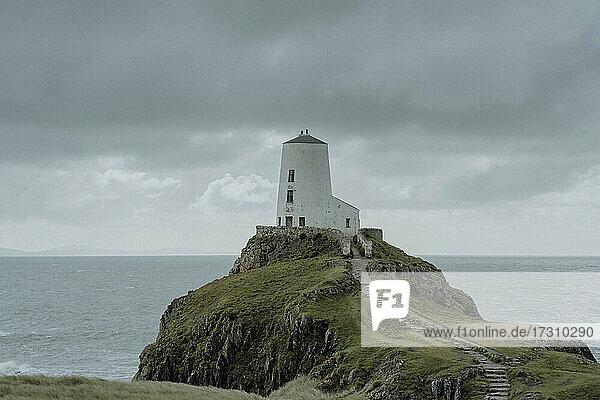Leuchtturm auf Meeresklippe unter bewölktem Himmel  Angelsey  Wales