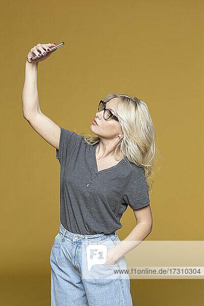 Studio Porträt Frau nimmt Selfie auf gelbem Hintergrund