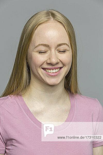 Porträt lachende junge Frau mit geschlossenen Augen