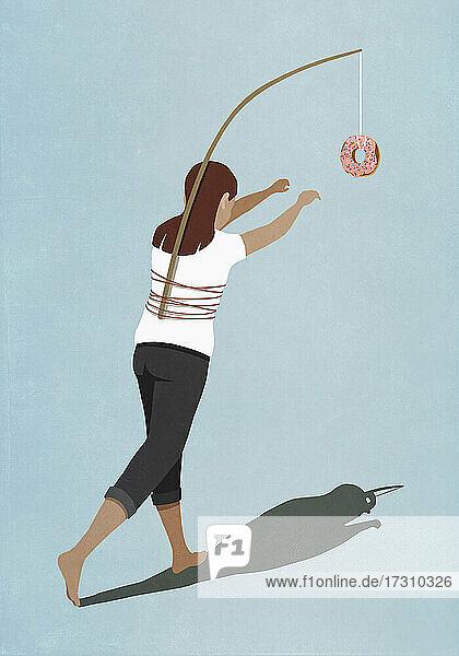 Frau jagt Donut an Stock gebunden auf dem Rücken