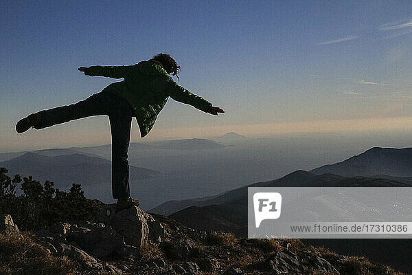 Verspielte Frau balanciert auf Berggipfel Felsen  Kvarner  Kroatien