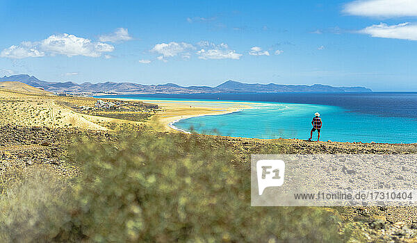 Tourist with straw hat looking at the ocean from Mirador Del Salmo viewpoint  Costa Calma  Fuerteventura  Canary Islands  Spain  Atlantic  Europe