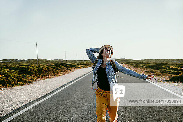 Happy woman holding hat while running on road