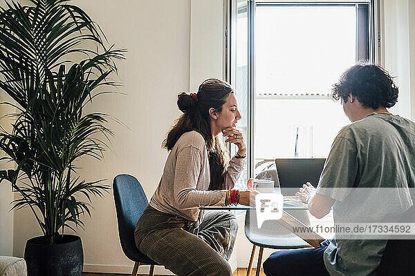 Frau mit Hand am Kinn  die einem Mann hilft  während er am Esstisch sitzt