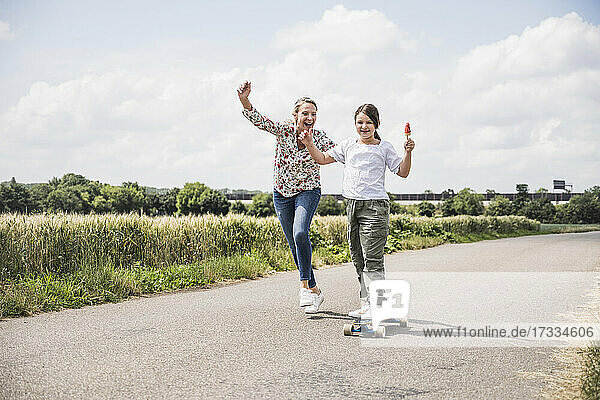 Woman cheering for girl on skateboard on road