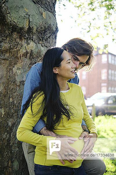 Mann umarmt schwangere Frau von hinten vor einem Baumstamm