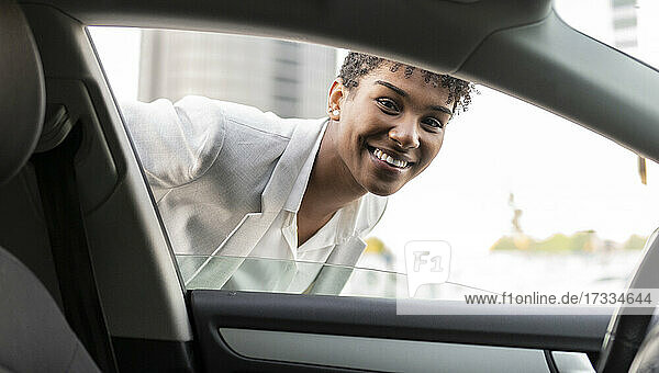 Smiling female professional looking through car window