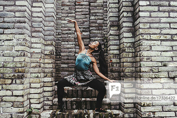 Young female dancer practicing dance amidst stone walls