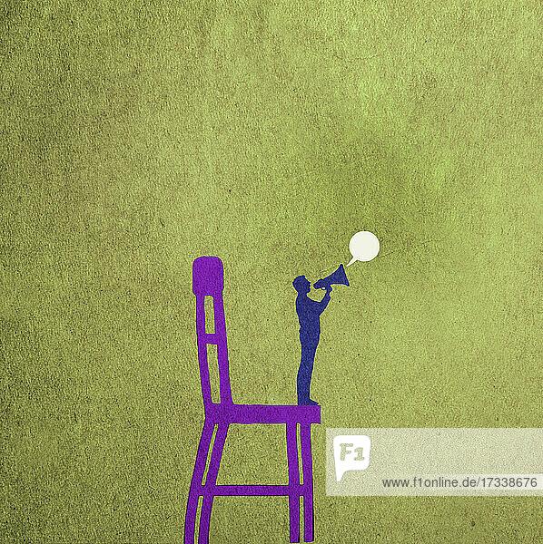 Kleiner Mann mit Megaphon auf einem großen Stuhl stehend