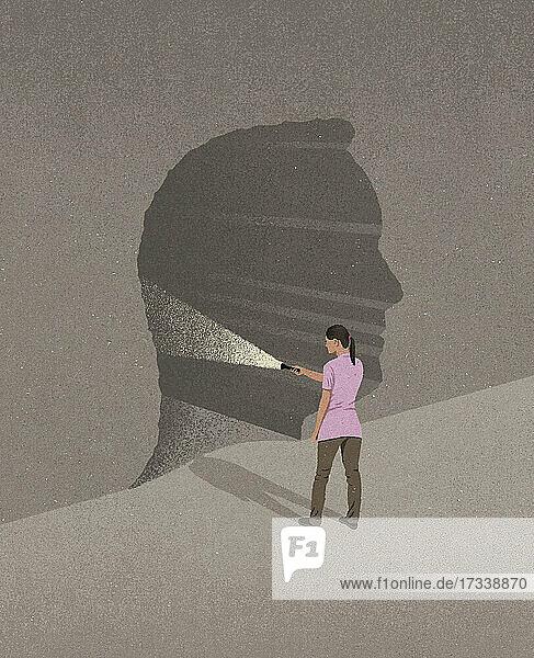 Frau leuchtet mit einer Taschenlampe in einen Tunnel in Form eines Männerkopfes