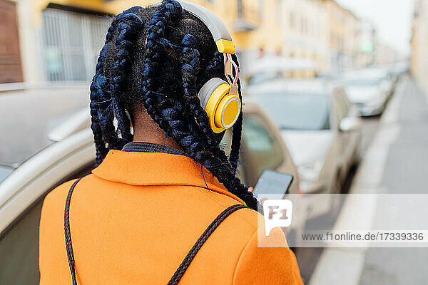 Italy  Milan  Rear view of woman with braided hair and headphones