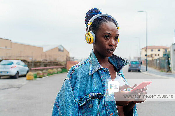 Italy  Milan  Woman with headphones holding smart phone in city