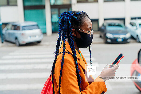 Italy  Milan  Fashionable woman with face mask holding smart phone on street