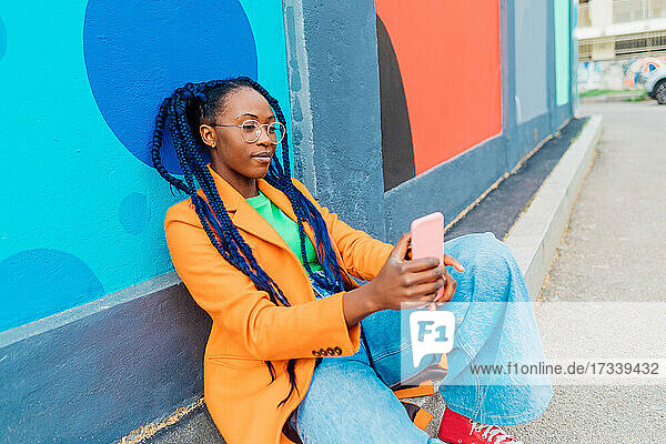 Italy  Milan  Woman with braids sitting by colorful wall  using smart phone