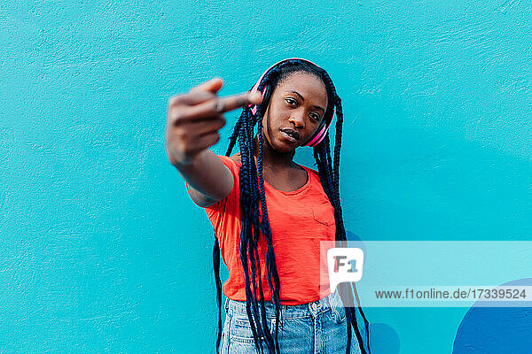 Italy  Milan  Young woman with headphones gesturing in front of blue wall