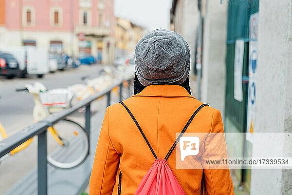 Italy  Milan  Rear view of woman in orange coat walking on sidewalk