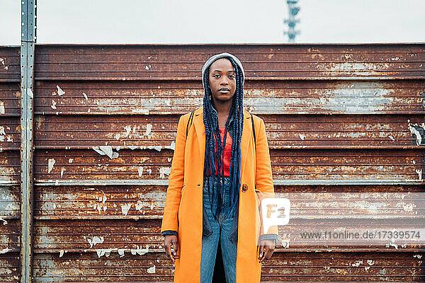 Italy  Milan  Portrait of woman in orange coat against rusty metal fence