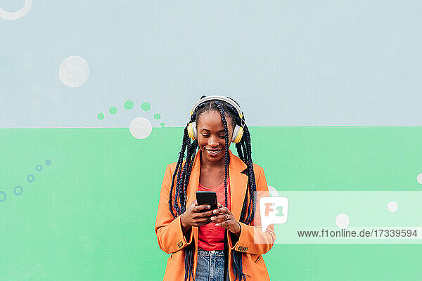 Italy  Milan  Stylish woman with headphones holding smart phone in front of wall
