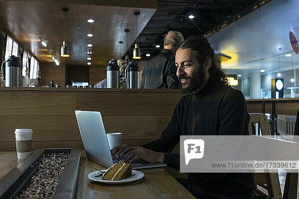 UK  London  Man using laptop at airport cafe