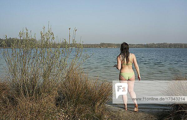 Netherlands  Noord-Brabant  Breda  Rear view of woman walking into lake