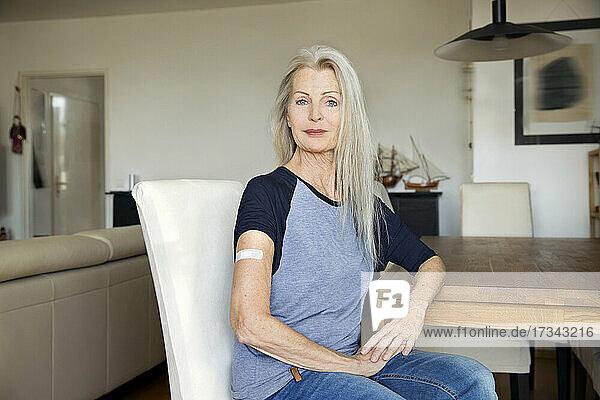 Austria  Vienna  Senior woman with adhesive bandage on arm sitting at table