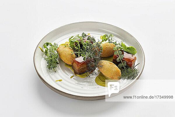 Glasierter Schweinebauch mit Kroketten und Kräutersalat