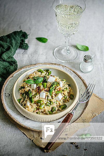 Risotto mit Spargel und veganem Fetaersatz serviert mit Weißwein