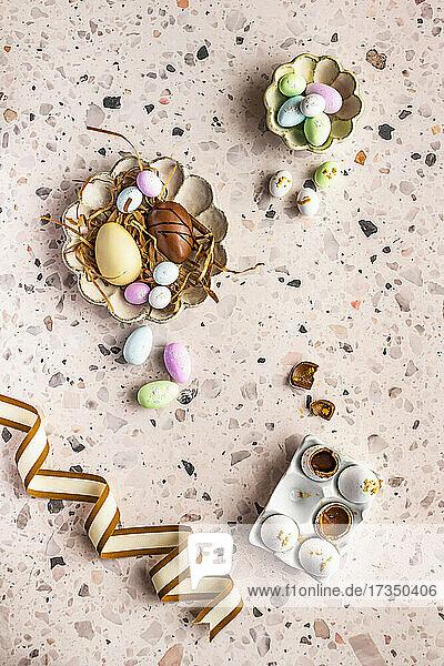 Verschiedene süße Ostereier in Eierschale und auf Tellern