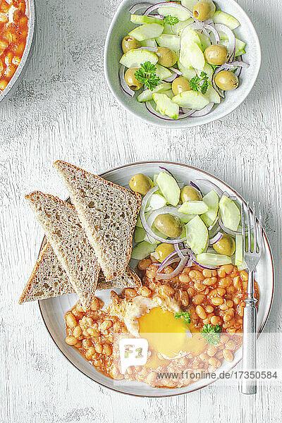 Bohnen in Tomatensauce mit Ei und Gurkensalat