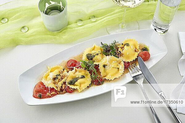 Ravioli mit geschmolzenen Tomaten  Kräutern und Pinienkernen